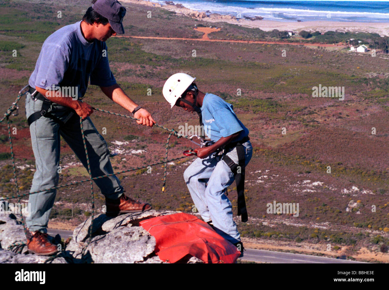 Kleinmond Western Cape South Africa 5 1998 n neducation young boy abseilling rocks water mountains ropes township - Stock Image