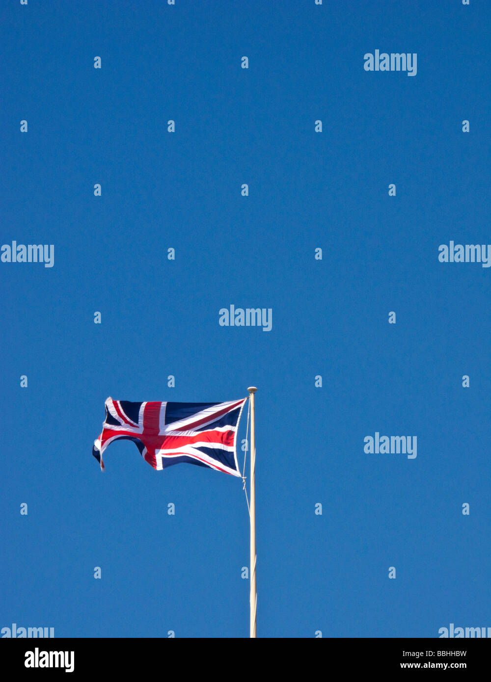 UNION FLAG FLYING ON A FLAGPOLE AGAINST A BLUE SKY - Stock Image