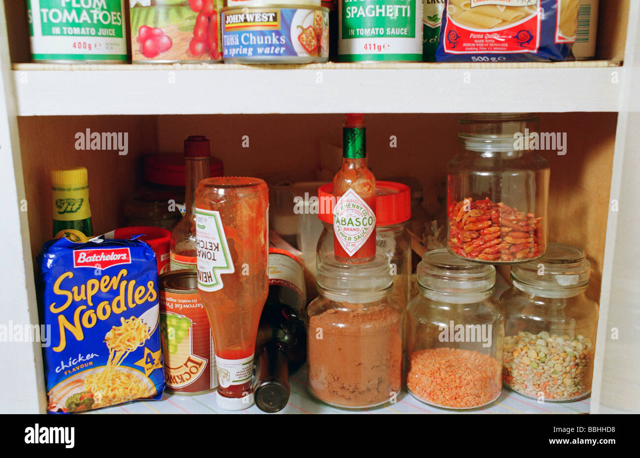 A food storage cupboard, kitchen cupboard, full of ingredients, dried and tinned food. A full pantry. - Stock Image