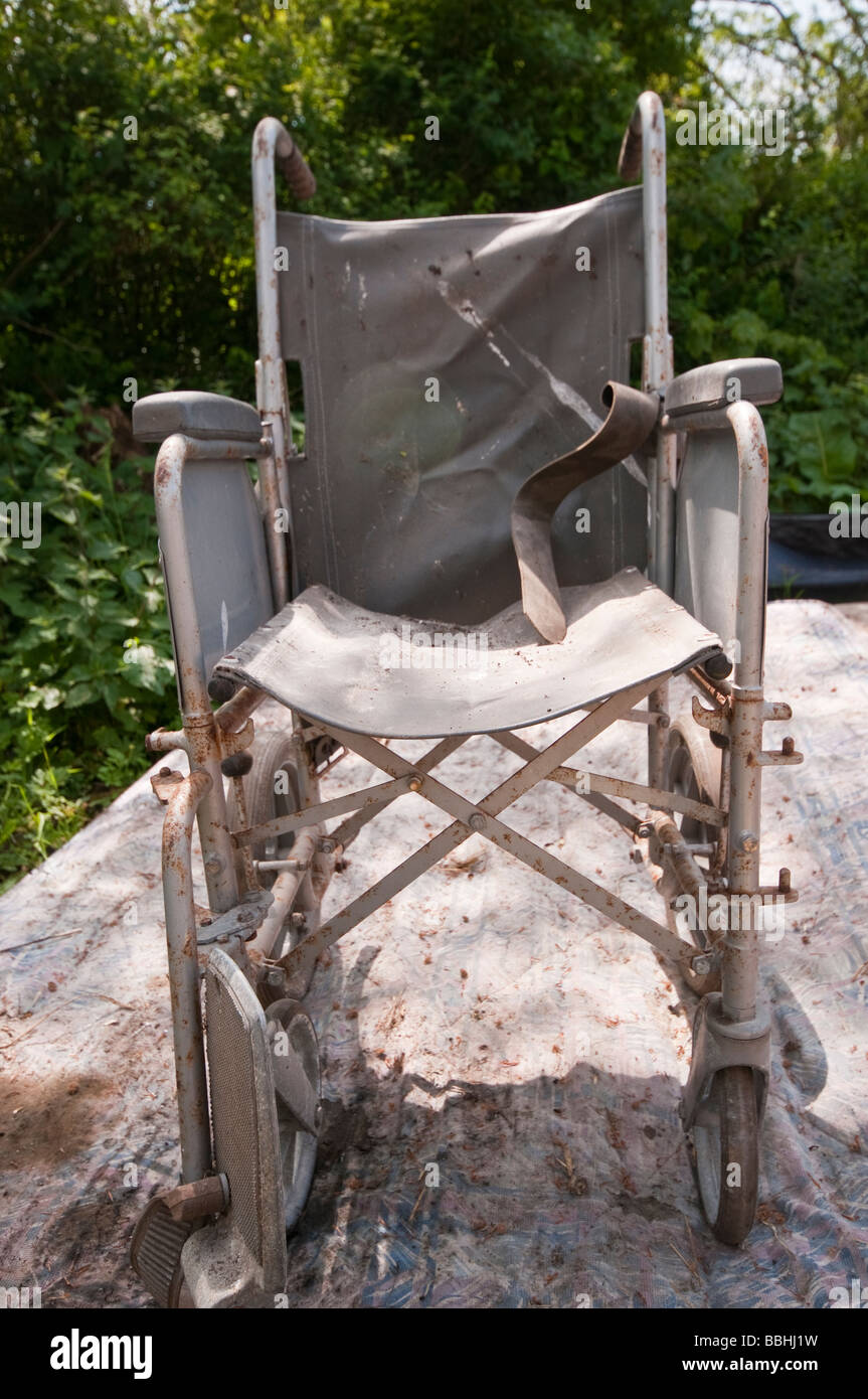 Abandoned wheelchair on an old mattress covered in dirt and rust - Stock Image
