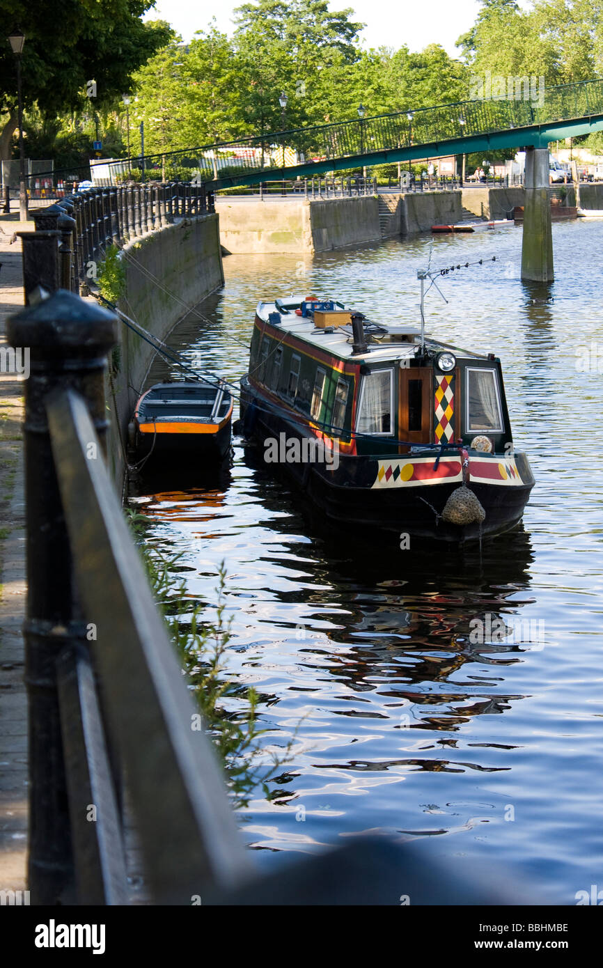 A longboat teathered to railings on the thames river, in Twickenham - Stock Image