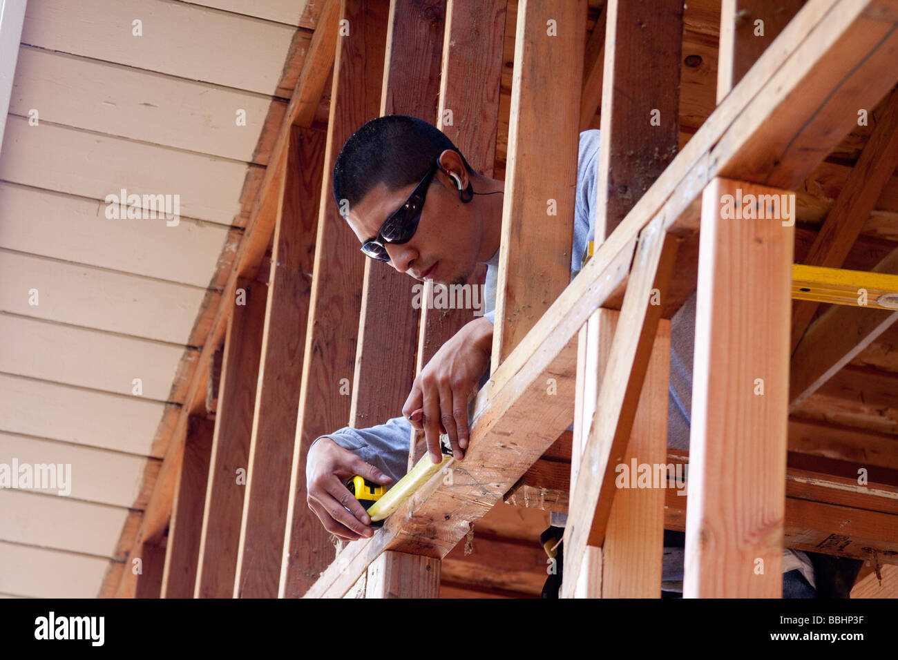 Mexican American carpenter using a measuring tape while doing rough ...