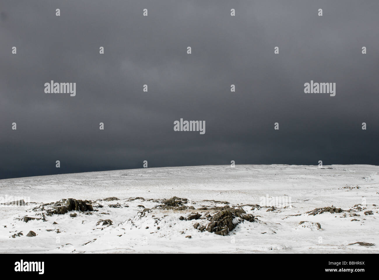 Bleak view over a snow covered mountain peak in the Lake District on a Winters day - Stock Image