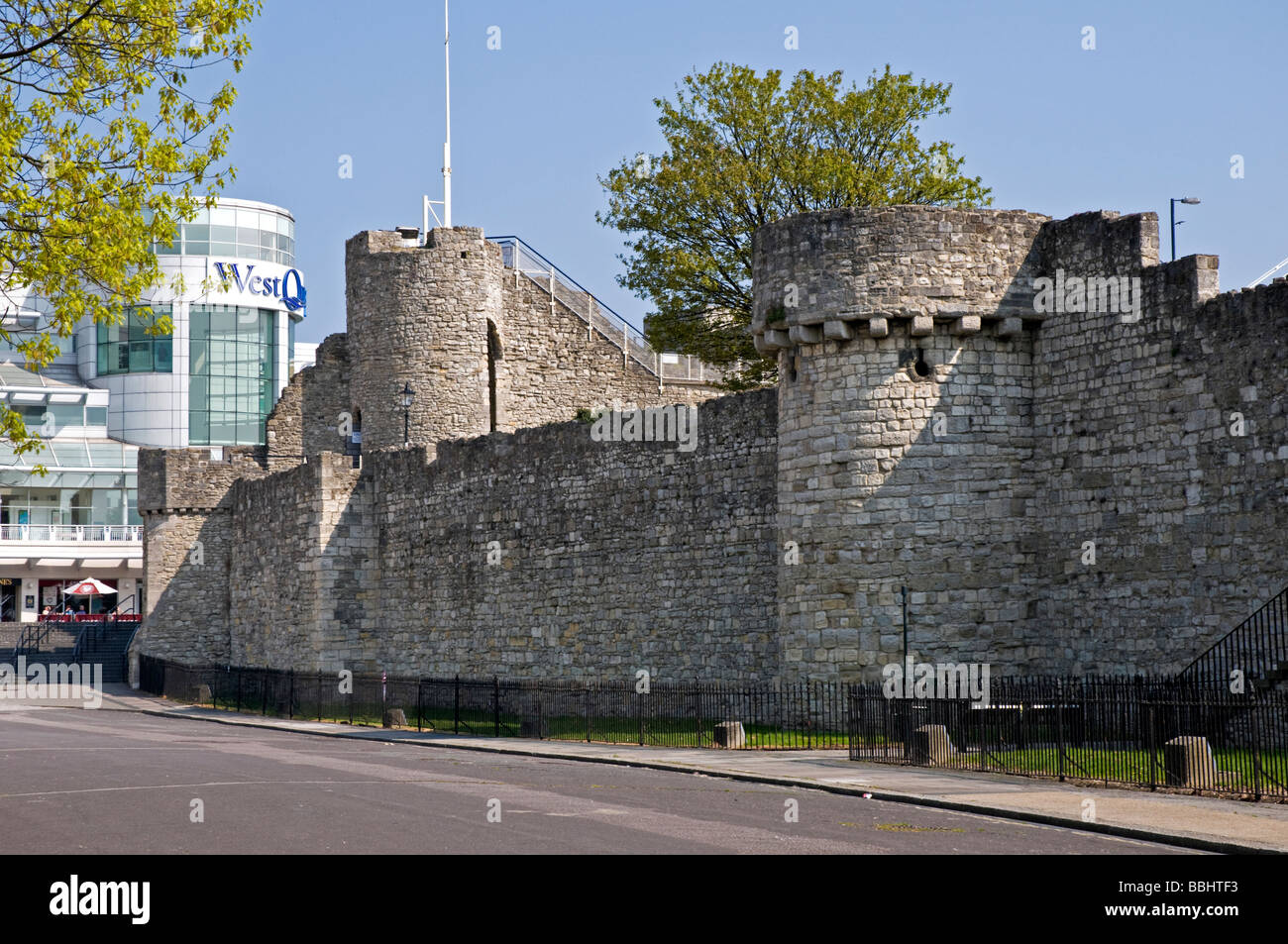 The medieval walls and towers of Southampton Castle contrast with the modern style of the shopping centre - Stock Image