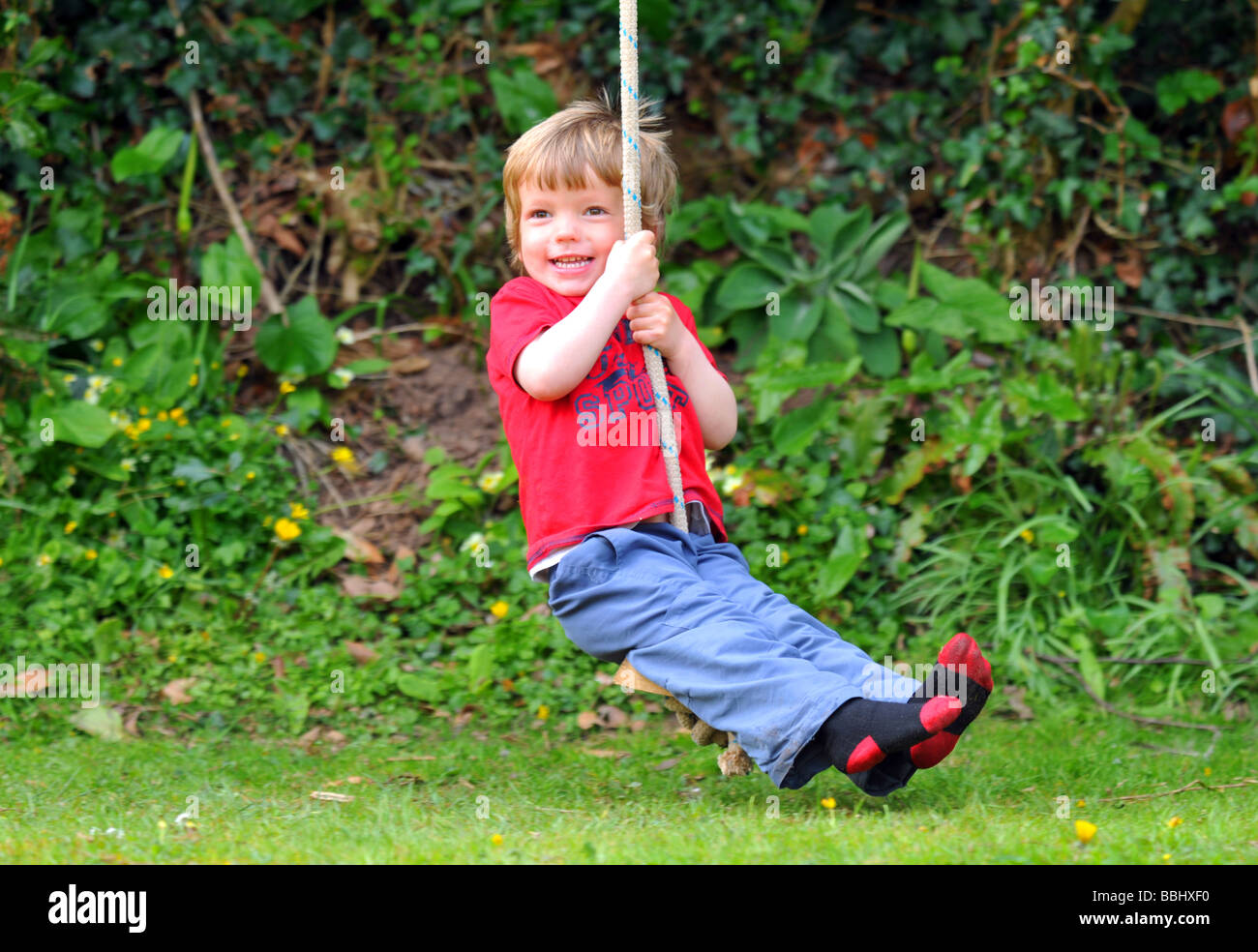Boy on a rope swing, child swinging on a rope - Stock Image
