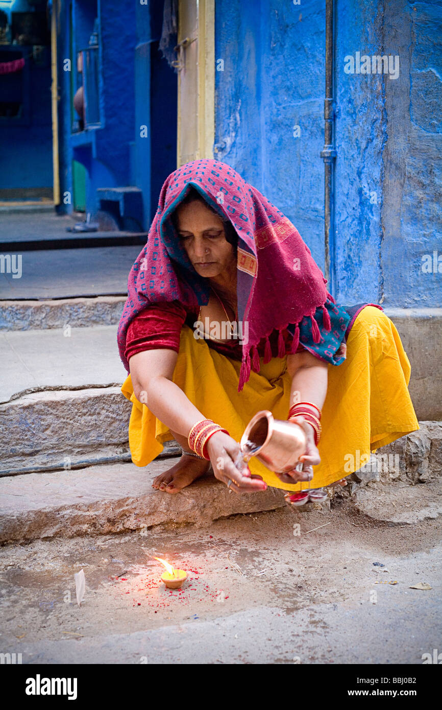 Jodhpur, India; Woman crouched over candle holding jug - Stock Image