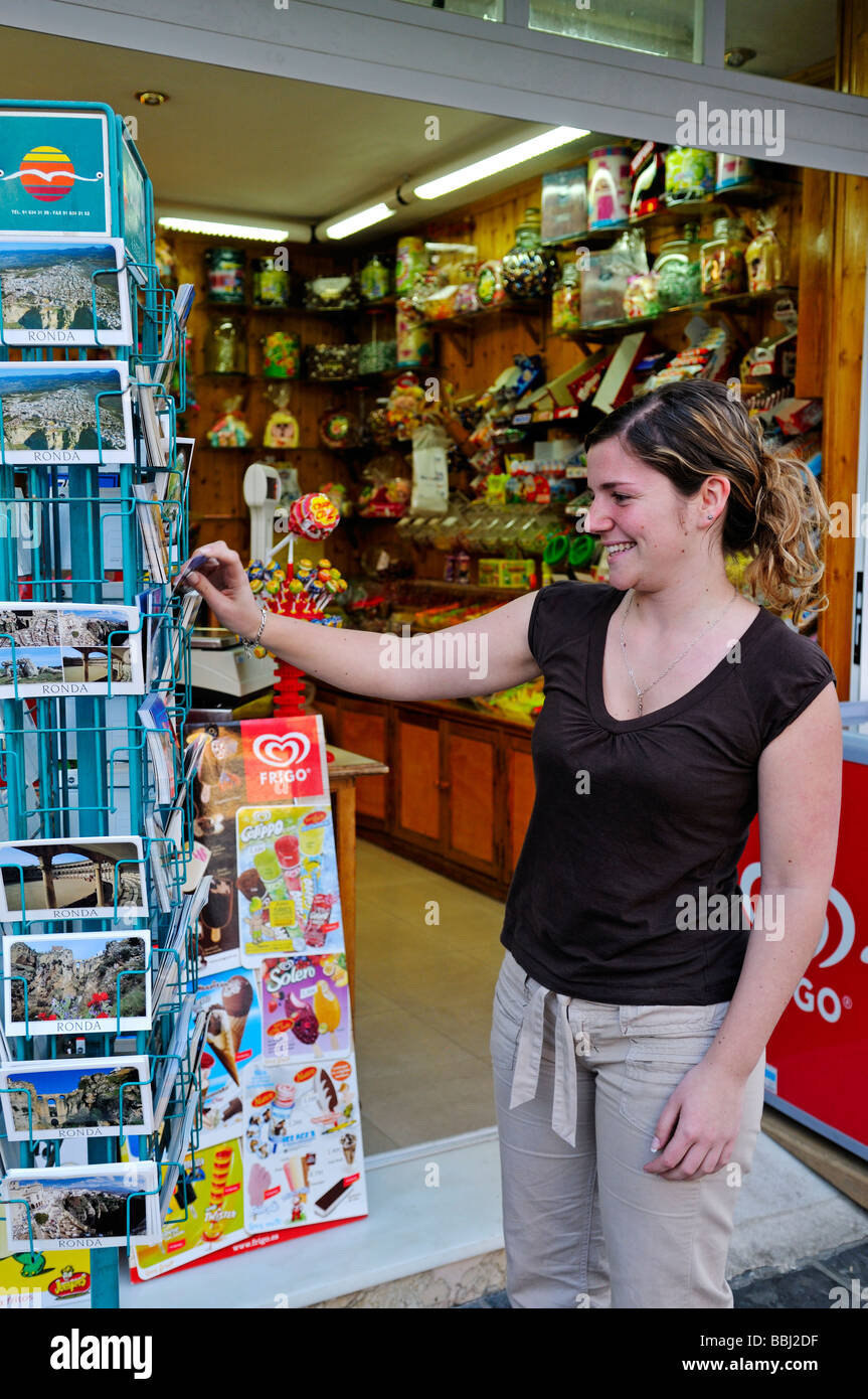 Woman looking at postcards outside shop in Ronda Spain - Stock Image