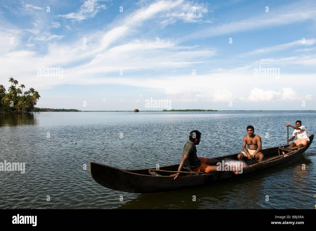 Fisherman fishing in rowing boat fishing on lake, backwaters kerala, India - Stock Image
