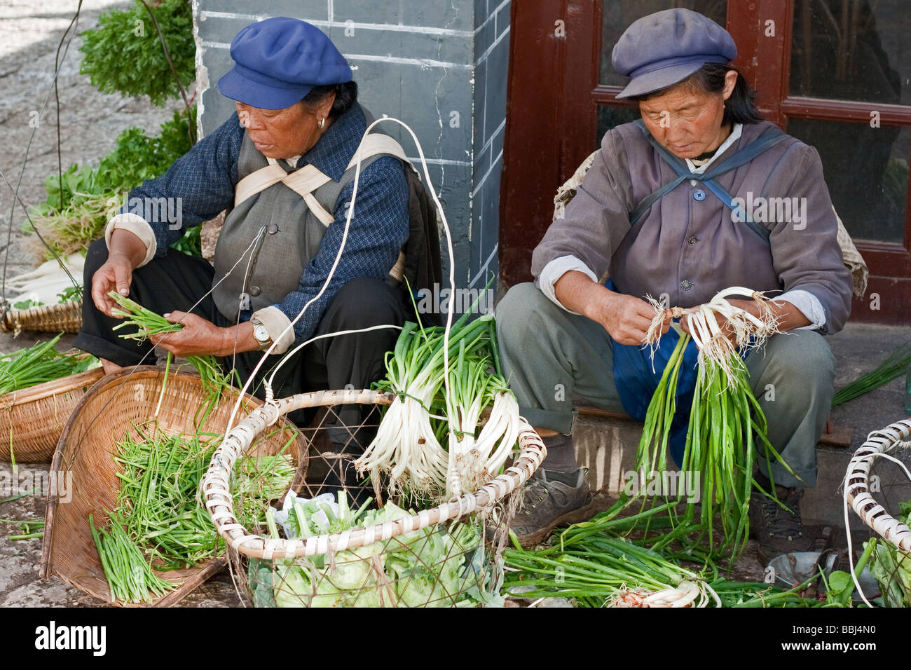 Two women of the Naxi tribe preparing vegetables for sale on the street at Lijiang old town, Yunnan, China - Stock Image