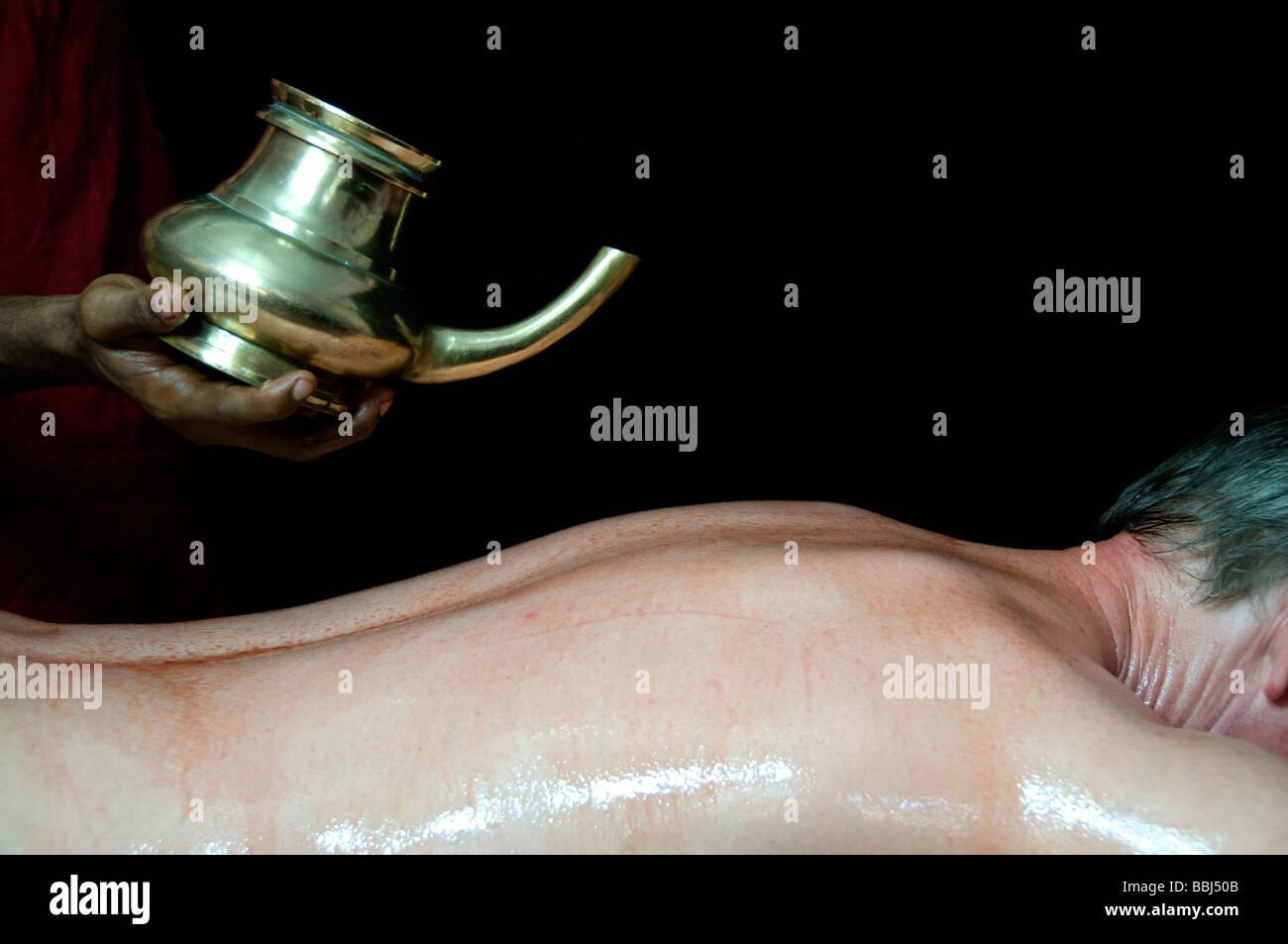 Young Man receiving an Ayurveda therapy, Ayurvedic massage treatment kerala India - Stock Image