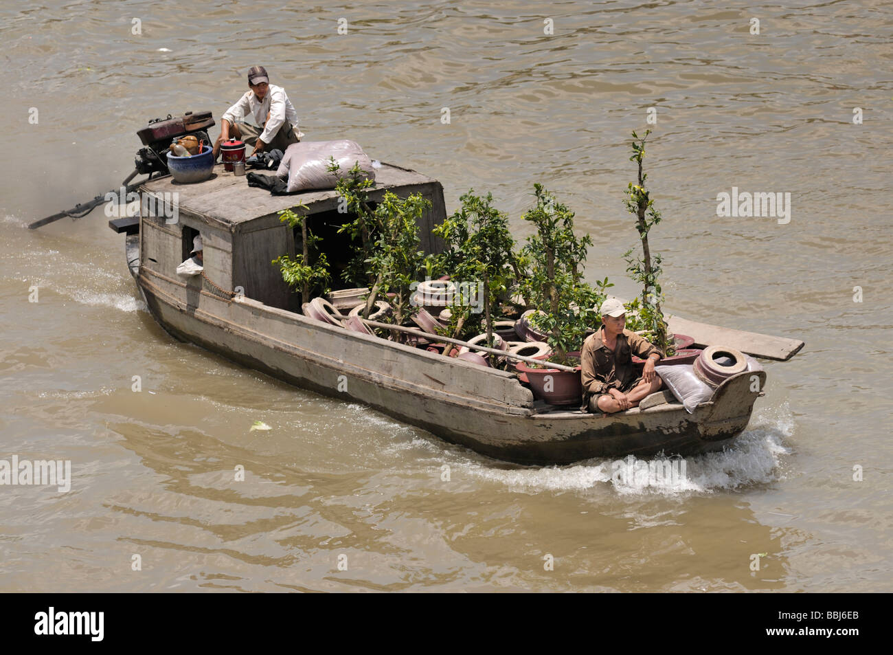Two men on a wooden boat on Mekong River, plant trader, Can Tho, Mekong Delta, Vietnam - Stock Image