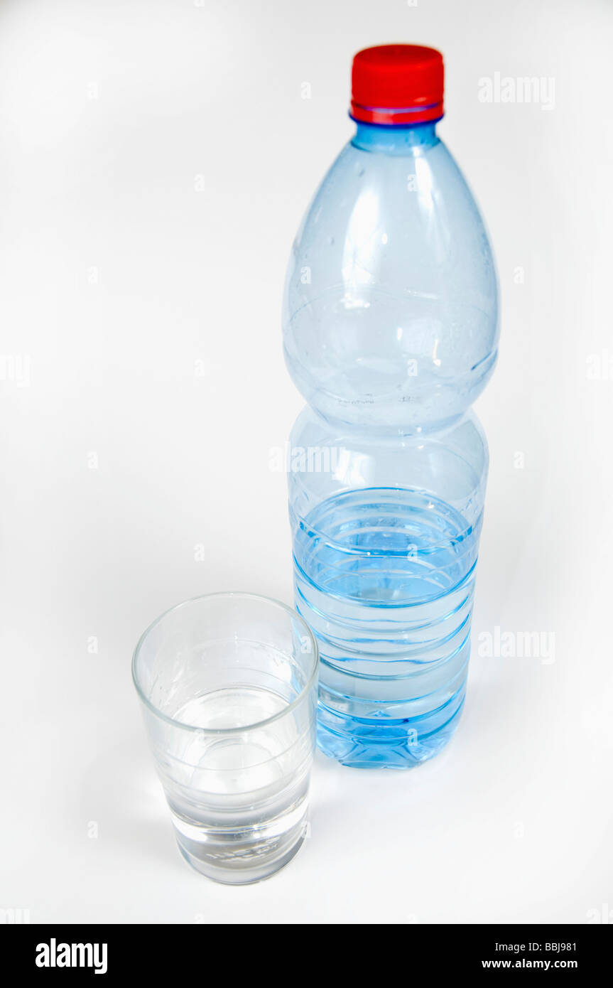 Cutout of a Plastic Bottle and glass of Mineral Water on white background - Stock Image
