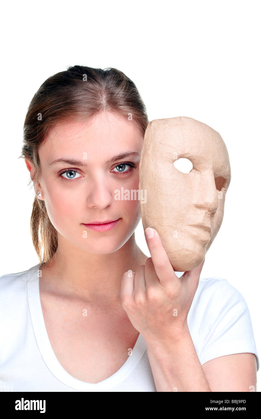 Young woman holding a mask in front of her face isolated on a white background - Stock Image