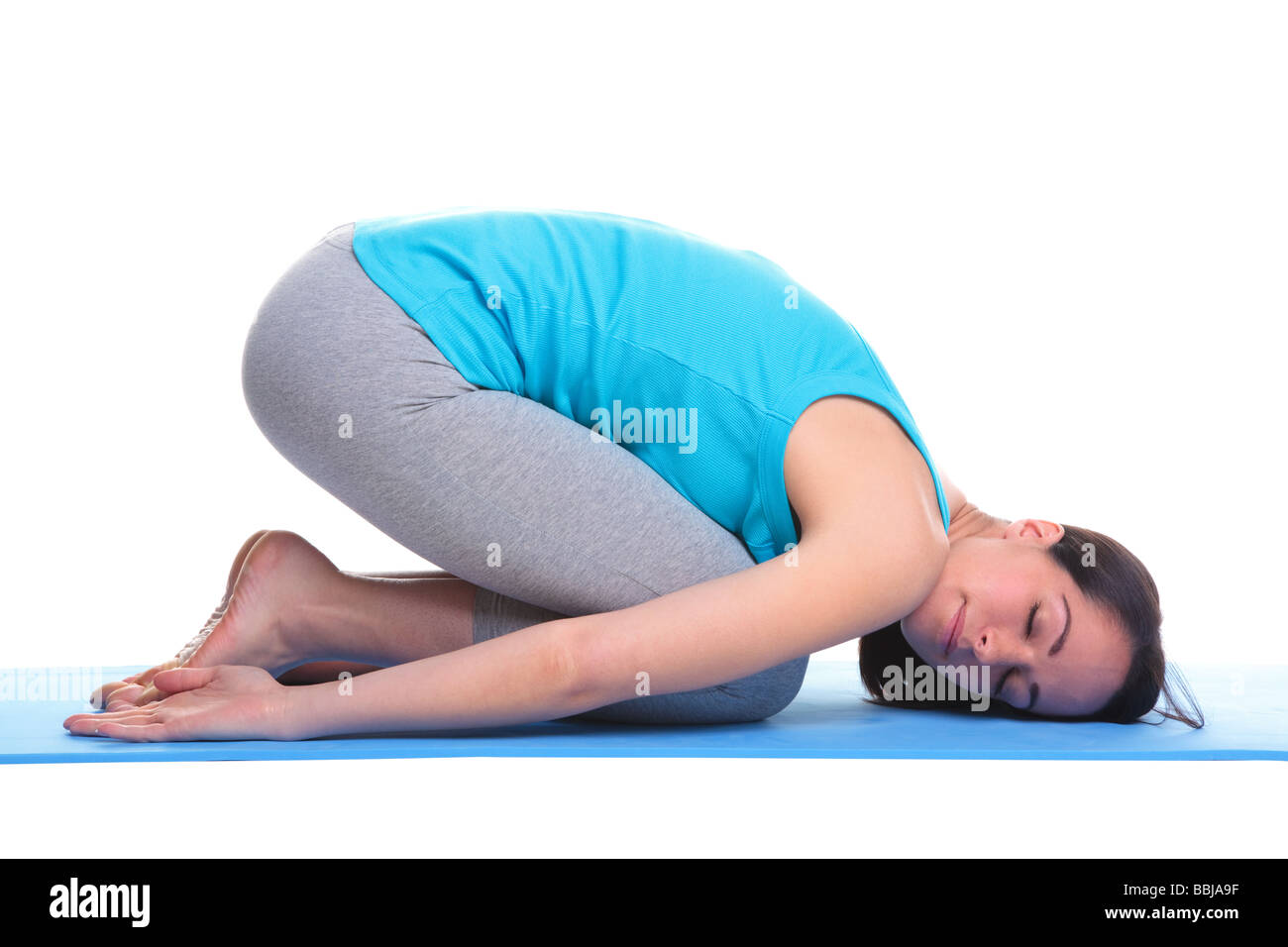Brunette woman on a yoga mat in a Balasana position also known as the Childs pose isolated on a white background - Stock Image