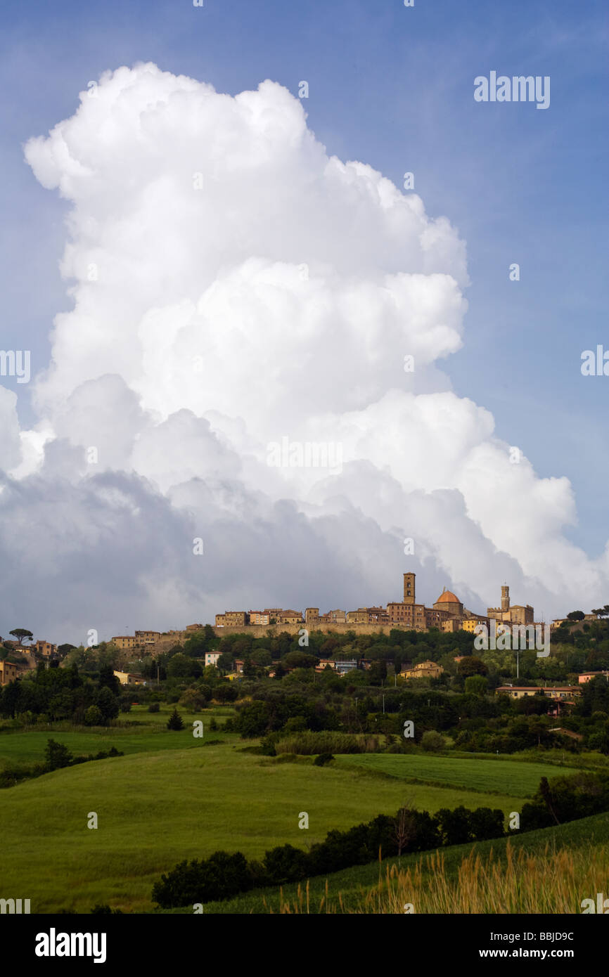 medieval city of Volterra on hill, huge cloud behind - Stock Image
