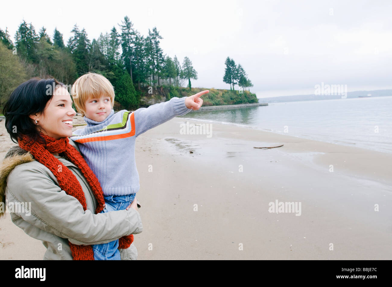 Boy with mother points out across water, Vancouver, British Columbia - Stock Image