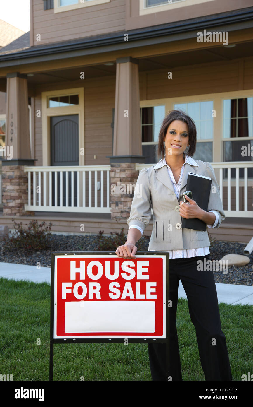Female Realtor standing by FOR SALE sign - Stock Image