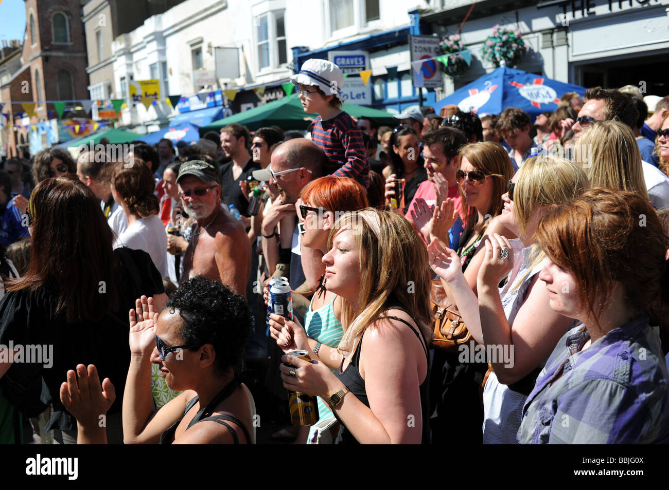 Crowds enjoy the bands performing and the hot weather at the Sunflower Street Party in Kemp town Brighton UK - Stock Image