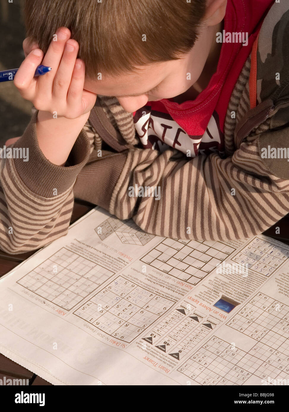 boy concentrating on suduko puzzle - Stock Image