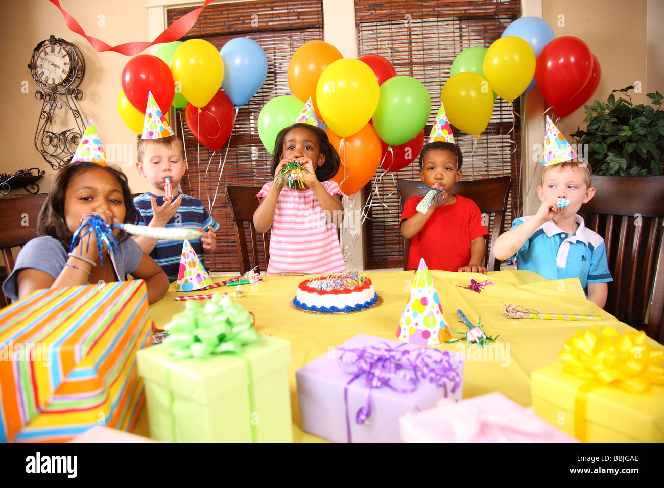 Children at birthday party blowing noise makers - Stock Image