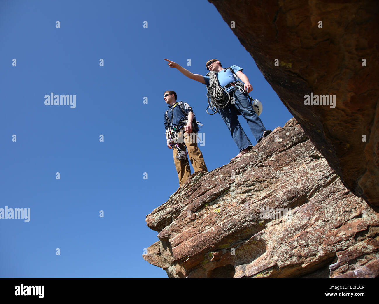 Two rock climbers standing on ledge - Stock Image