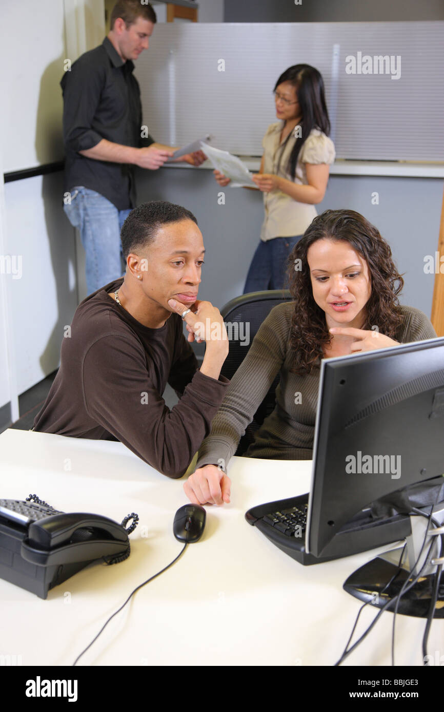 Two businesspeople at computer in foreground with co workers in background - Stock Image