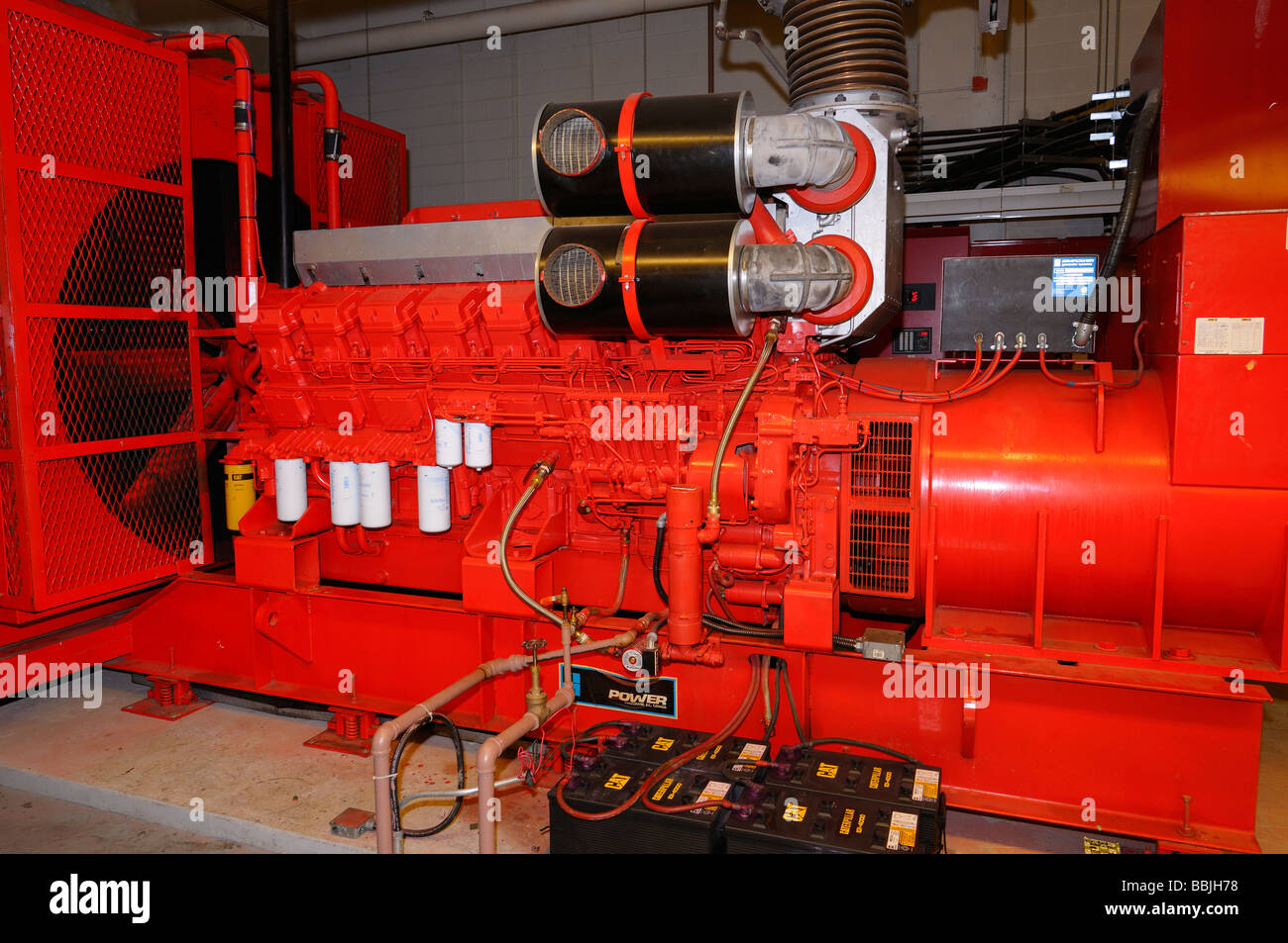 Large diesel engine for backup power on roof of highrise office building - Stock Image