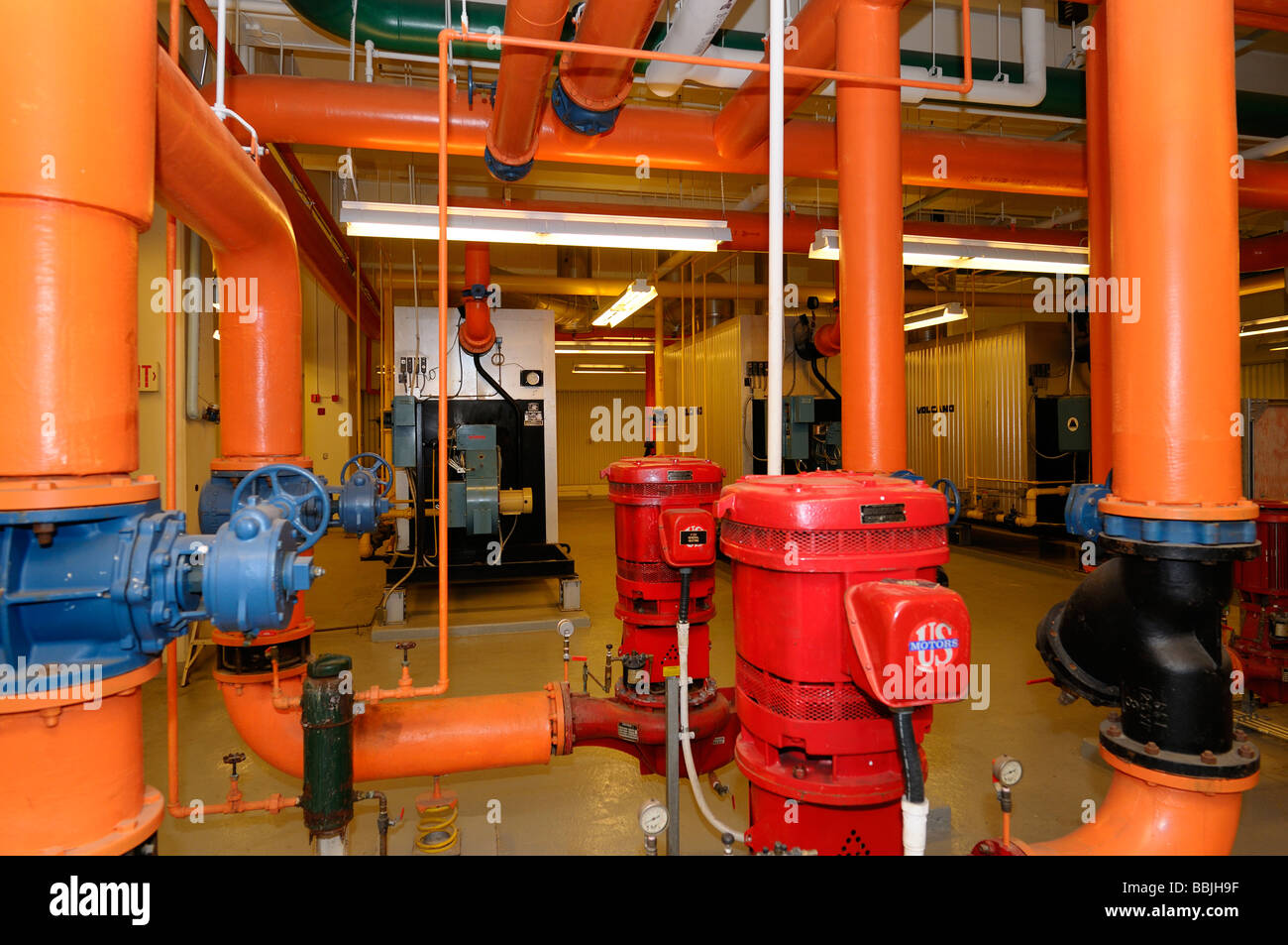 Row of furnaces and hot water pipes painted orange in the boiler room of a highrise office building - Stock Image