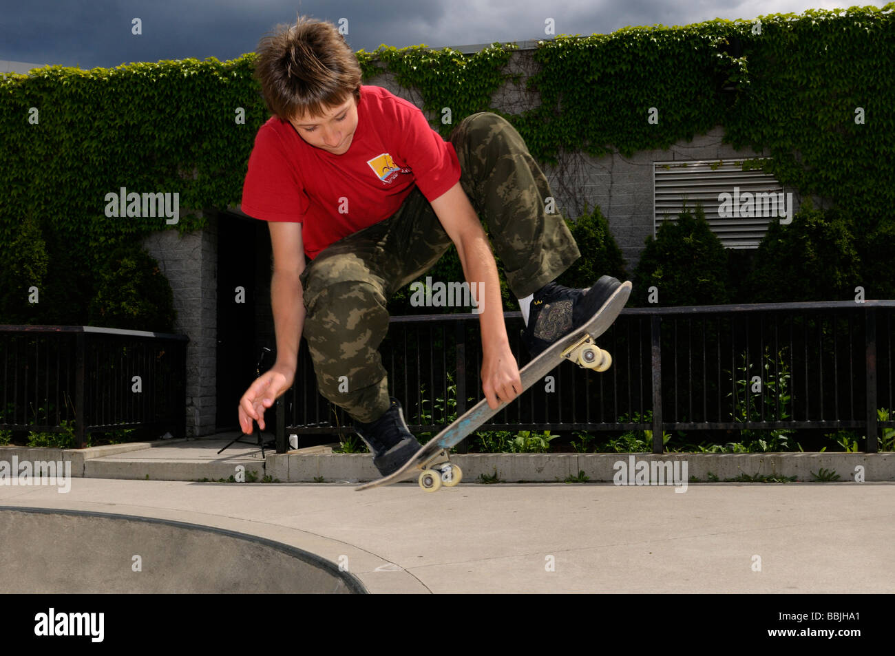 Airborne boy doing a mute grab Slobair on a skateboard above a concrete bowl at a Toronto outdoor Park - Stock Image