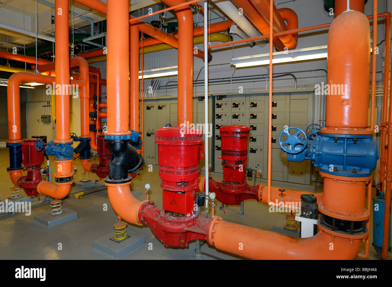 Electrical heating control and orange water pipes in the boiler room of a highrise office building Toronto - Stock Image