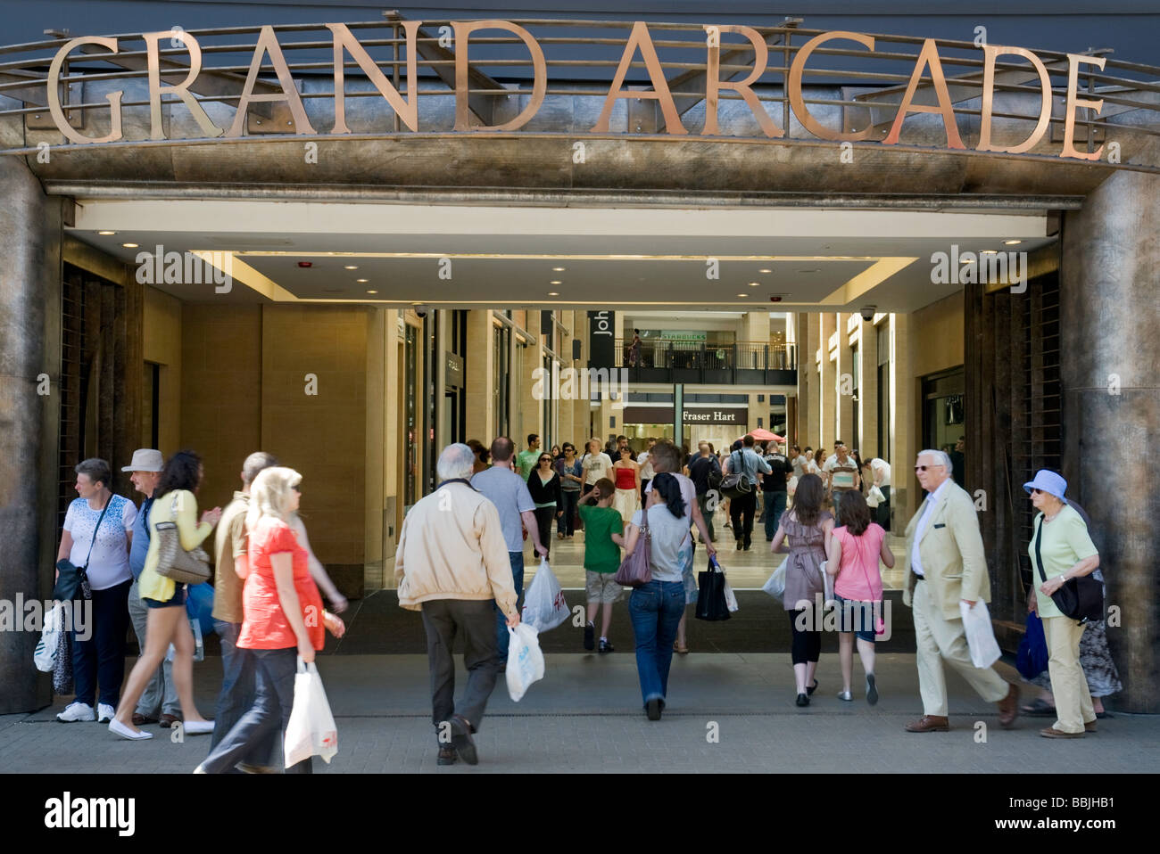 Crowds of shoppers on a sunny day entering the Grand Arcade shopping mall,  Cambridge, UK - Stock Image
