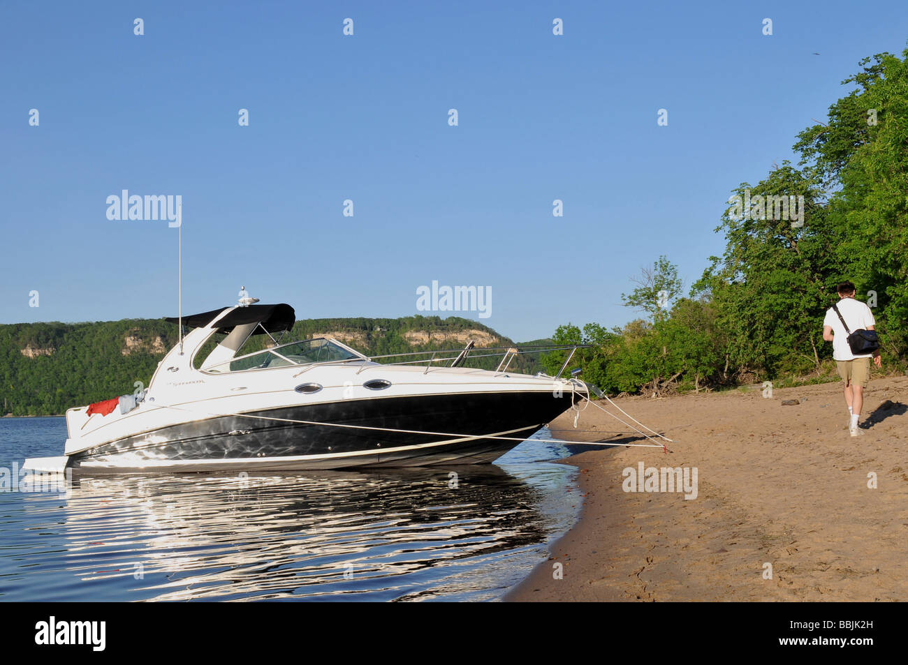 Anchored boat on sandy beach. - Stock Image