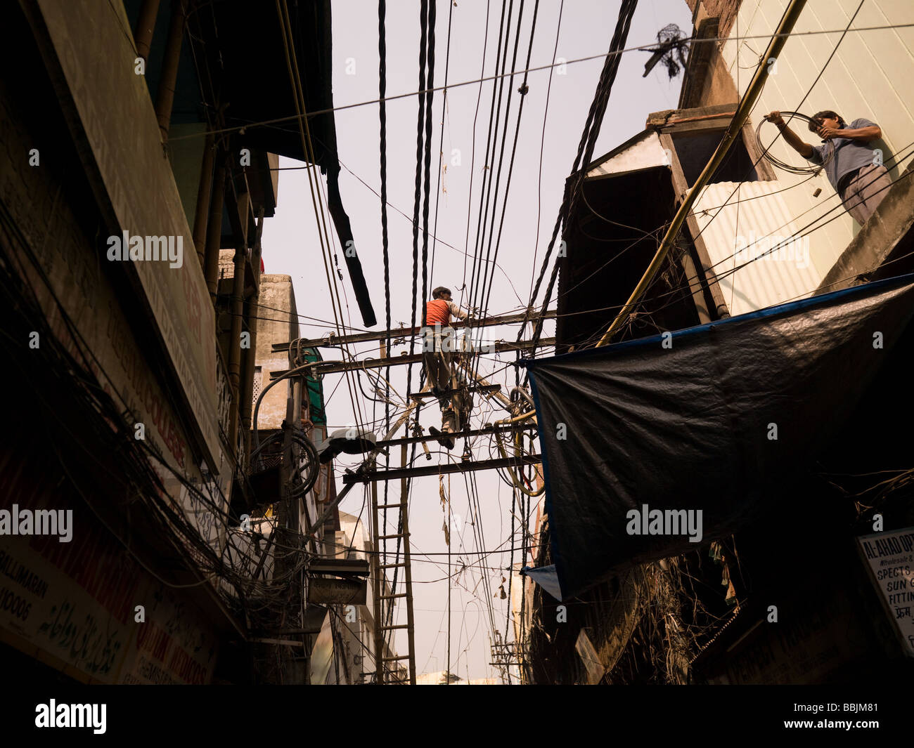 Repairmen working on overhead wires in Delhi India Stock Photo