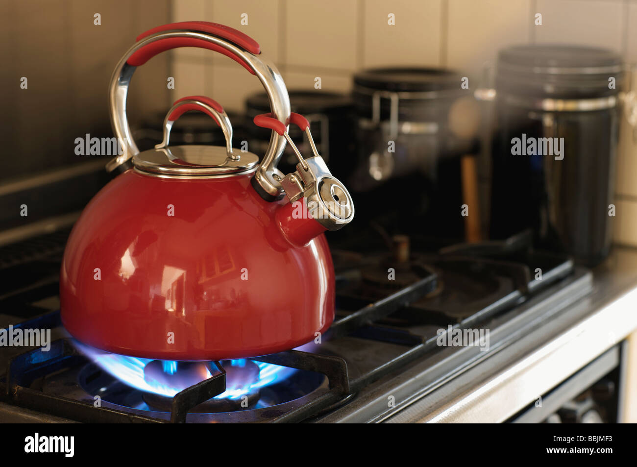 a-red-teapot-boiling-on-a-gas-stove-BBJM