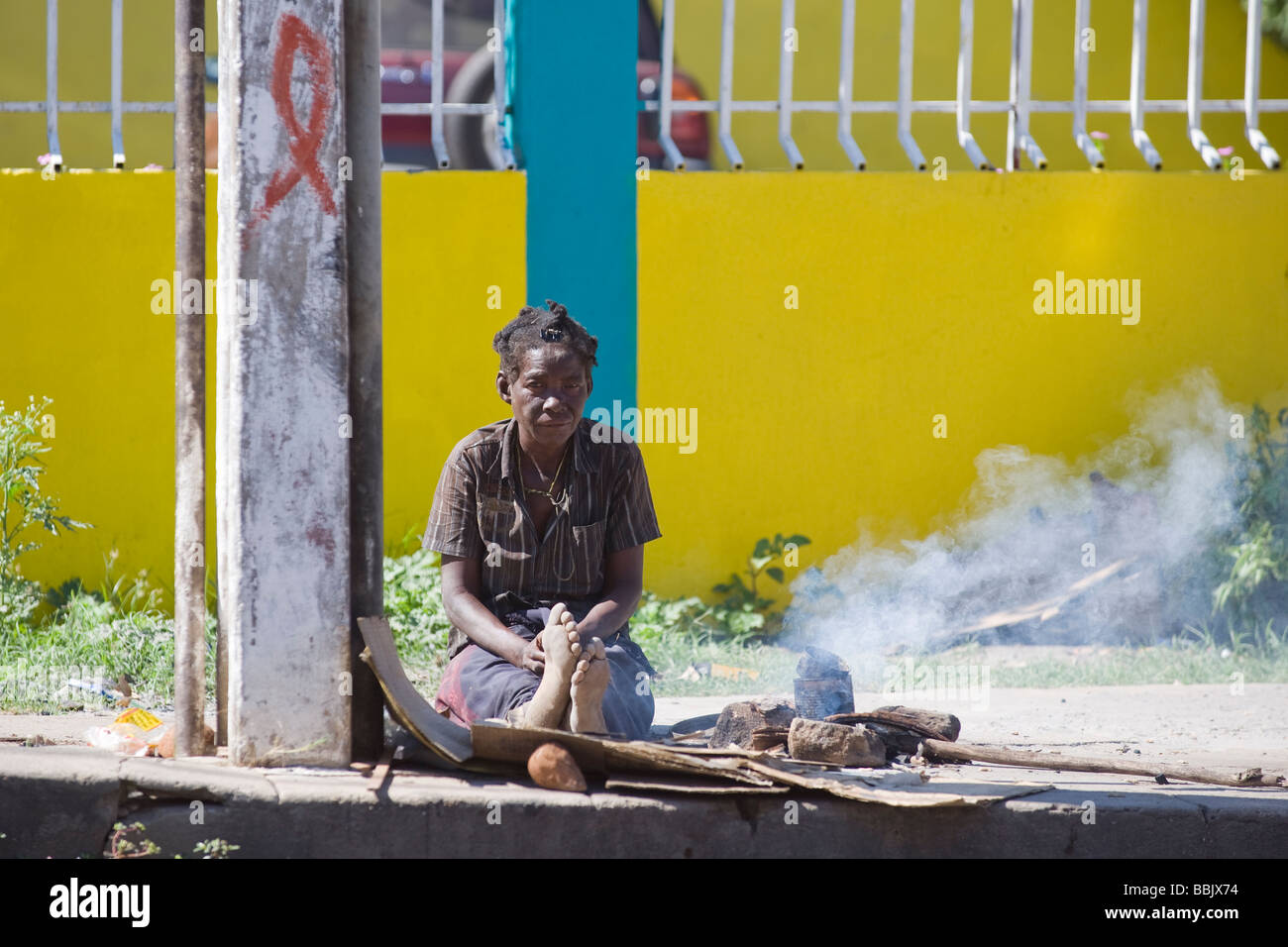Homeless woman cooking on the sidewalk Quelimane Mozambique - Stock Image