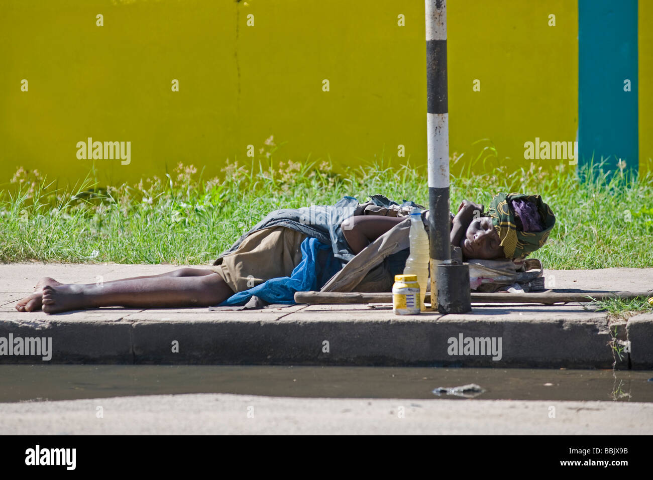Homeless woman sleeps on the sidewalk Quelimane Mozambique - Stock Image