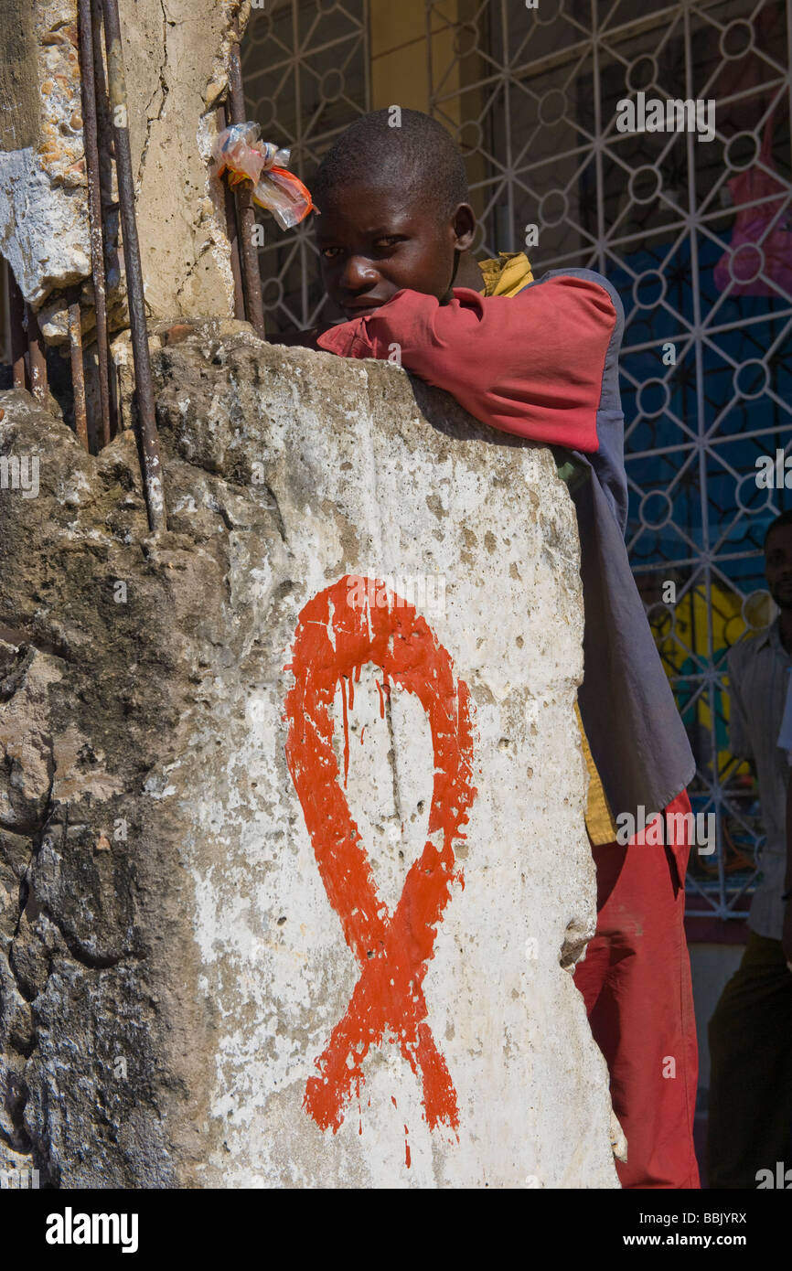Boy standing at a pillar with painted HIV AIDS ribbon Quelimane Mozambique - Stock Image