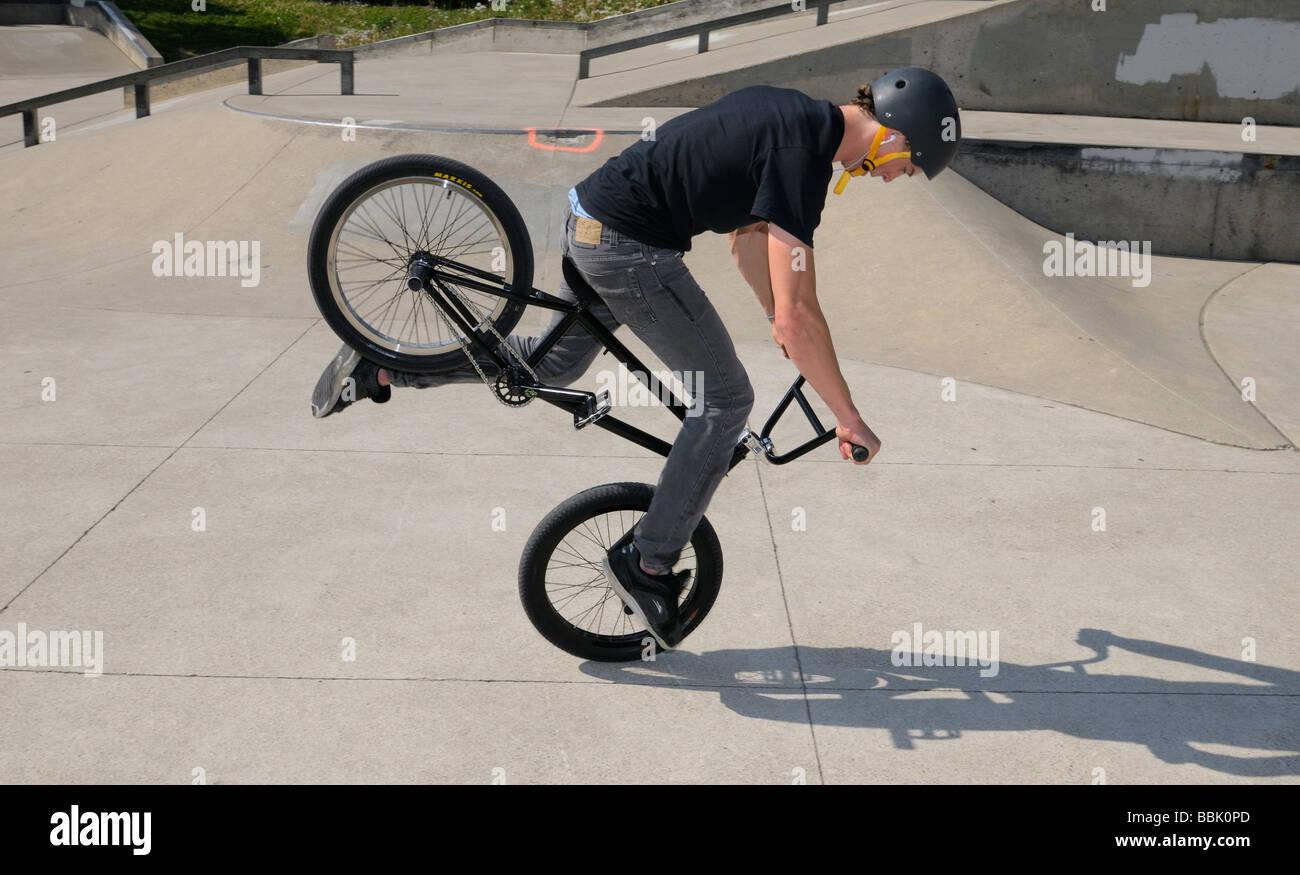 Flatland BMX bike rider doing a Nose Manual Dork Wheelie trick on front wheel Toronto Canada - Stock Image