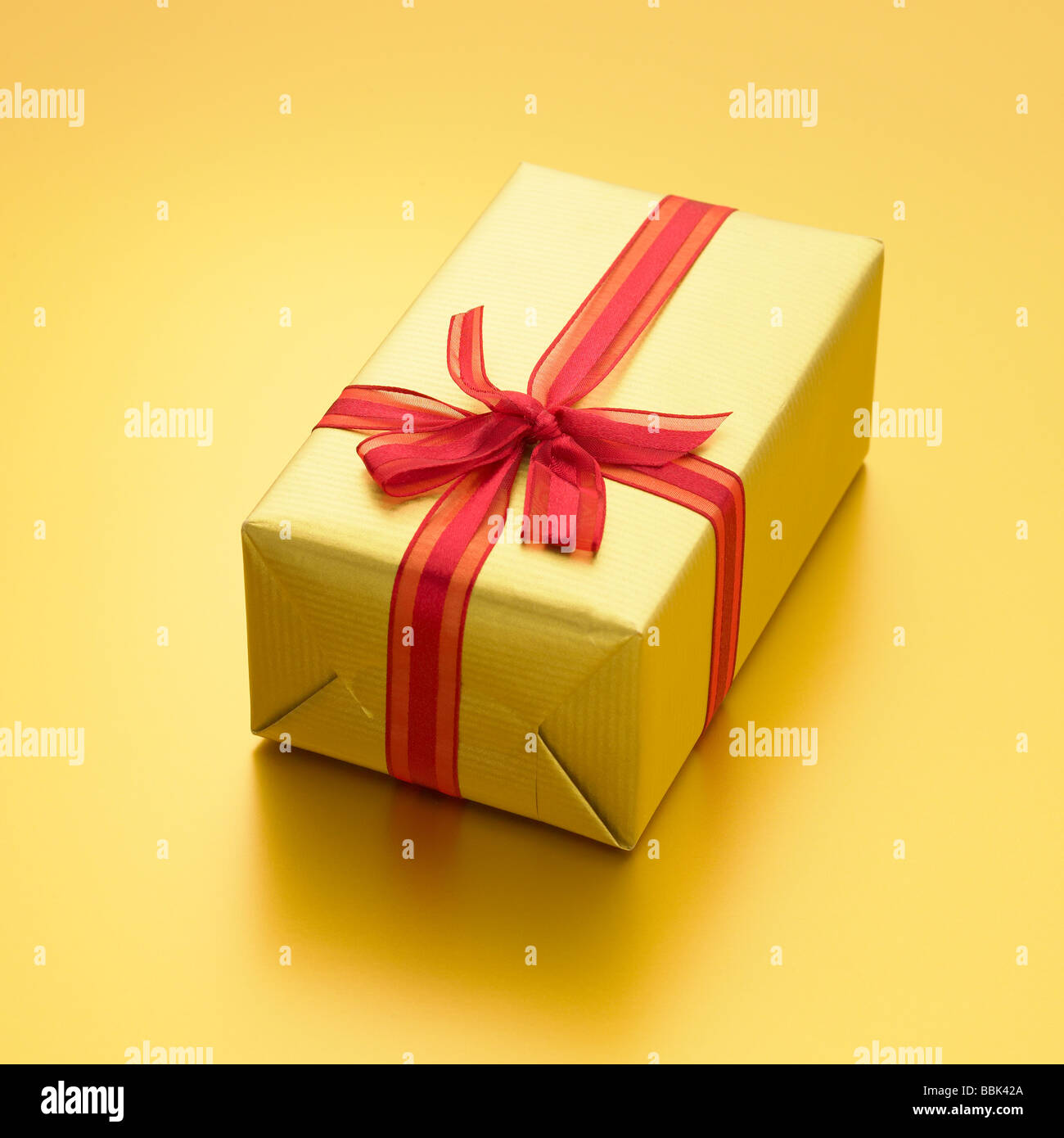 Luxury gold present with red ribbon on gold background. - Stock Image