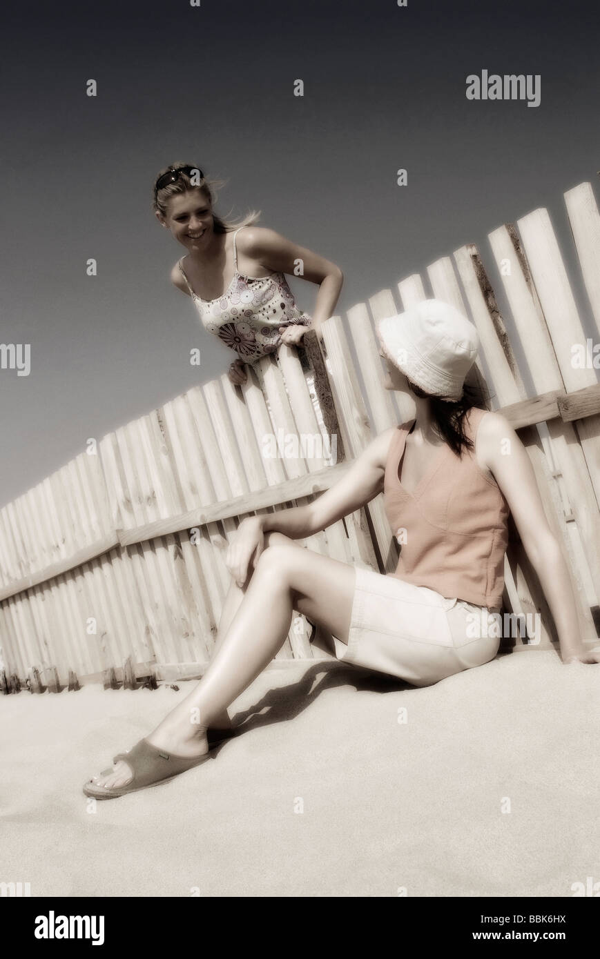 Two pretty young women relaxing on a windy beach in lovely sunlight at Trafalgar beach in southern Spain shot with - Stock Image