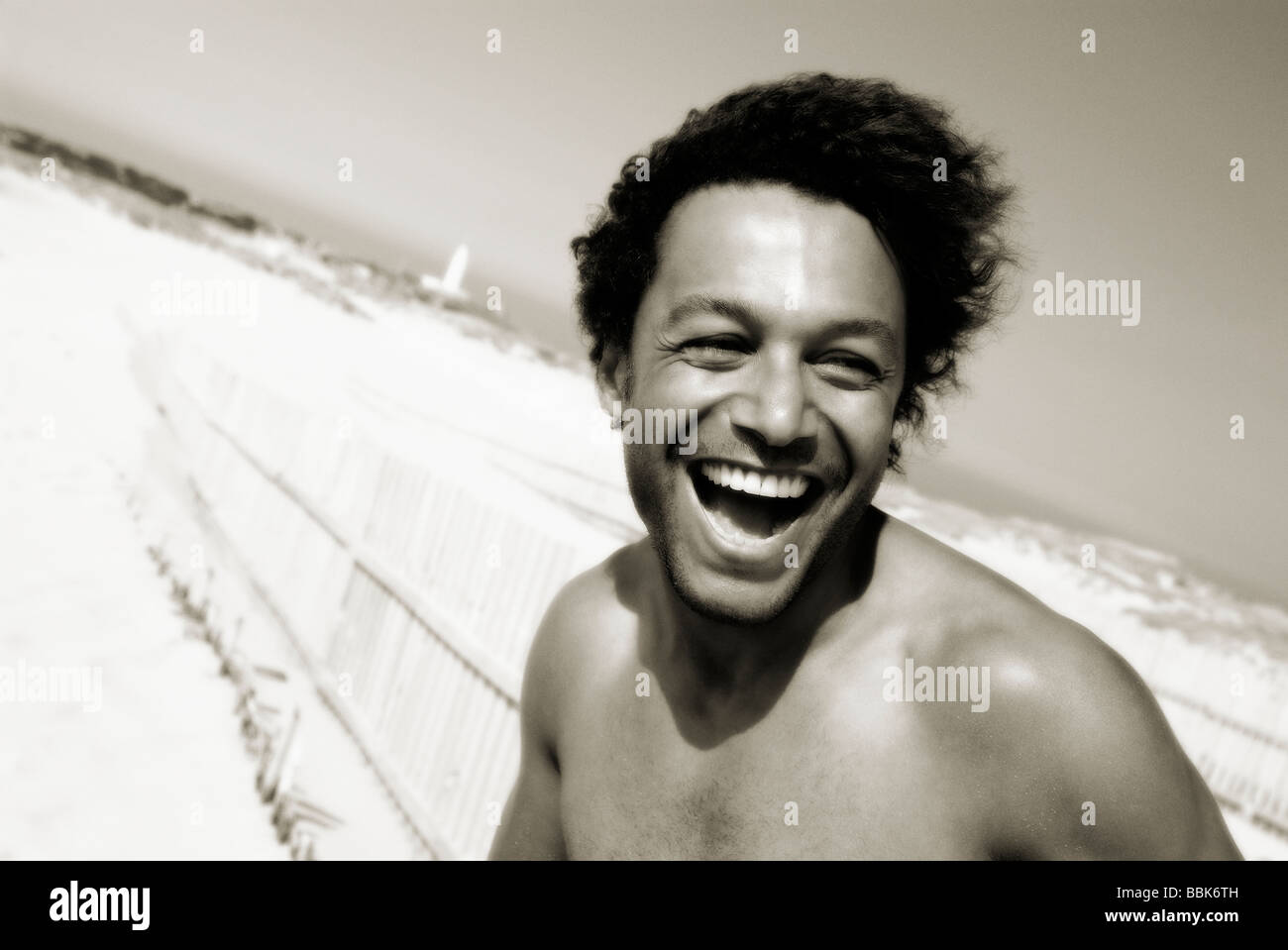 A monotone portrait of a young mixed race man on Trafalgar beach in southern Spain looking at the camera and laughing - Stock Image