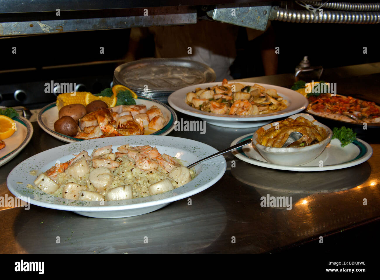 Cooked seafood entrees under warmer ready for serving at ...