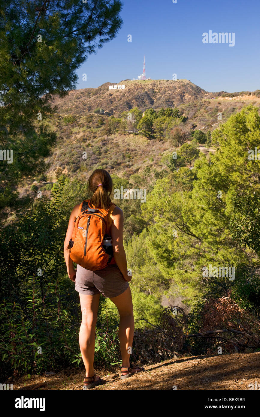 A hiker stops to look at the Hollywood sign from the Mt Hollywood Trail in Griffith Park Los Angeles California - Stock Image