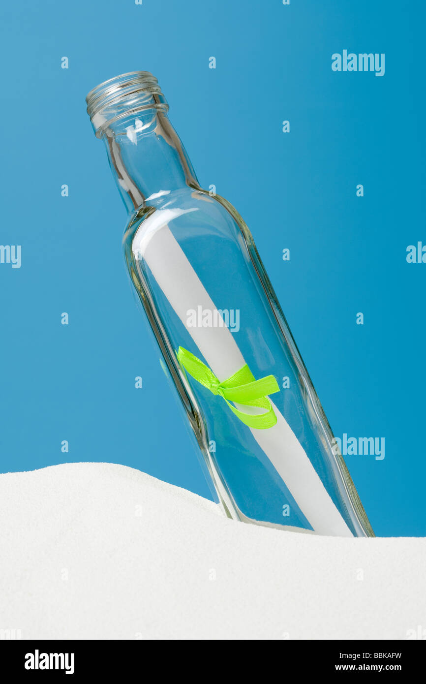 a message in a bottle on white sand stock image