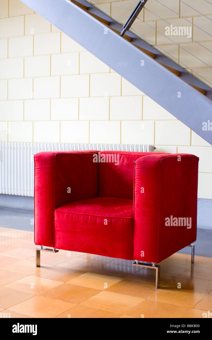 Red armchair and stairs in a modern apartment - Stock Image