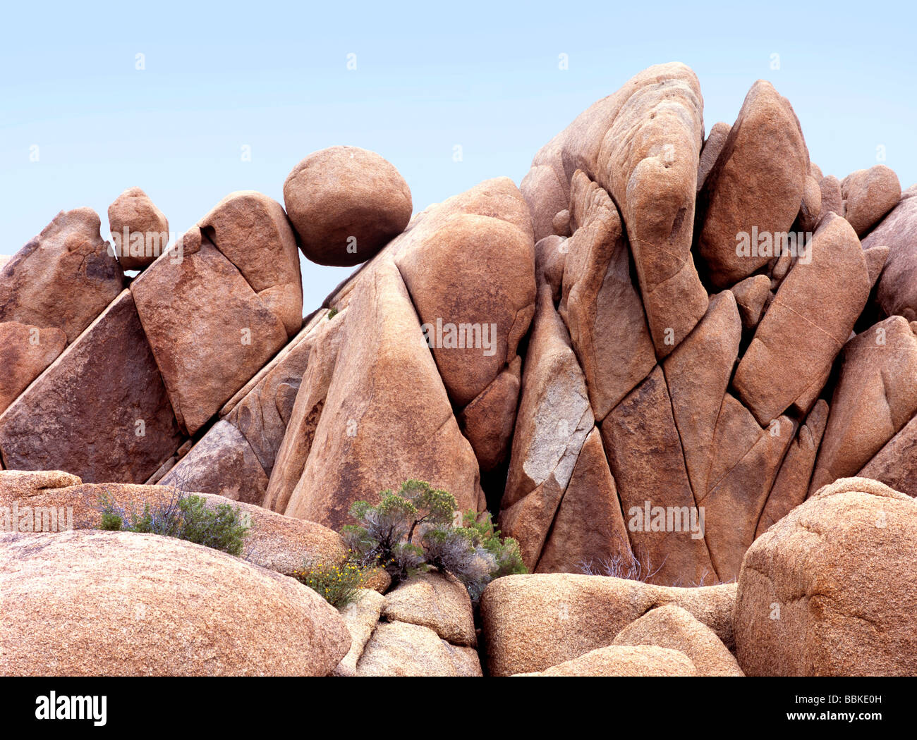 This round boulder over four feet in diameter is balanced on a rocky pile in Joshua Tree National Park California - Stock Image