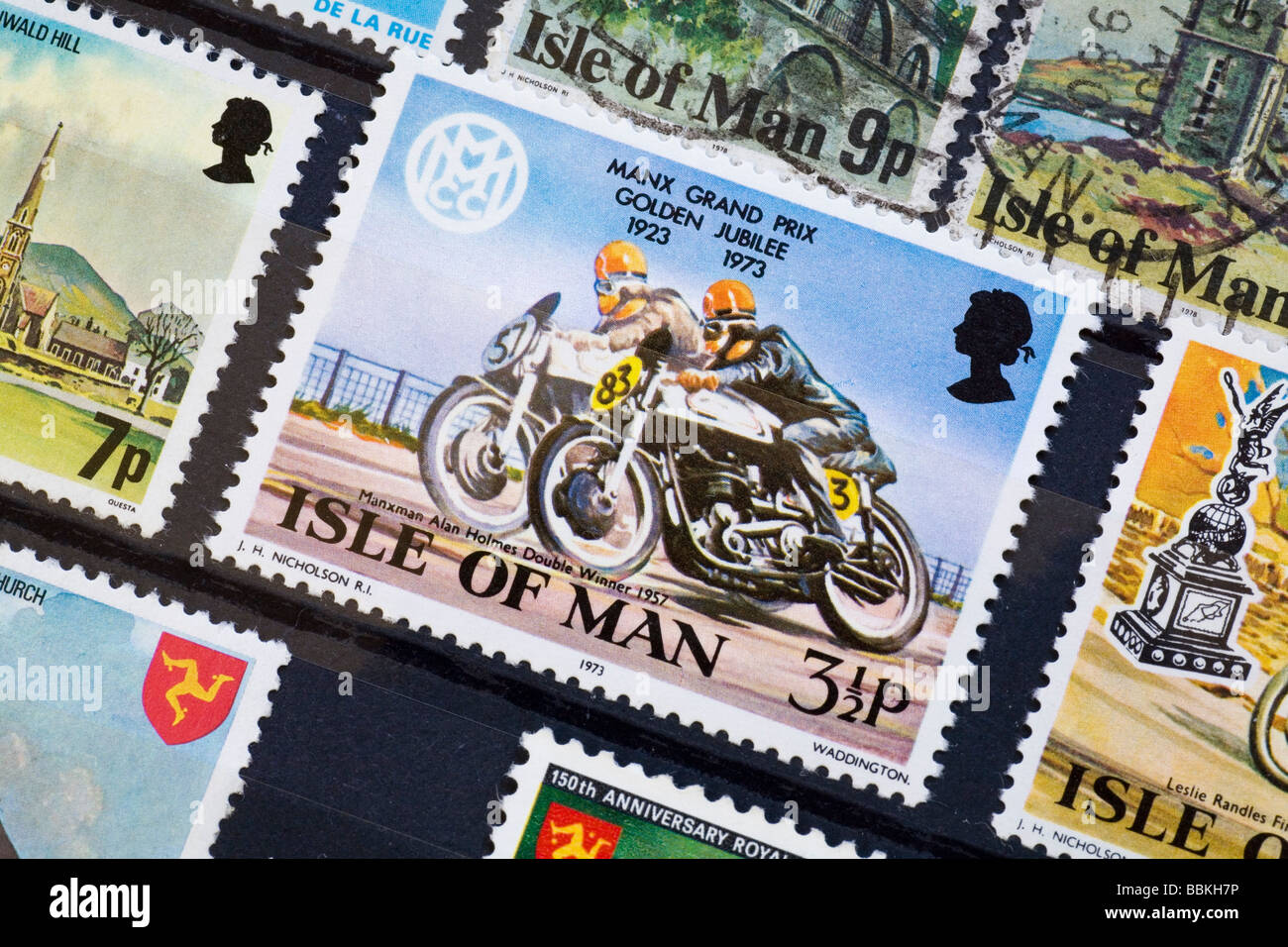 1973 Isle of Man commemorative Manx Grand Prix postage stamp in amongst other Isle of Man stamps in a stamp album - Stock Image