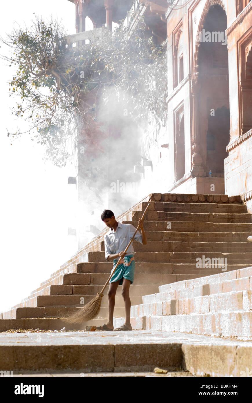 Low caste man sweeping a bathing ghat in Varanasi, India. - Stock Image