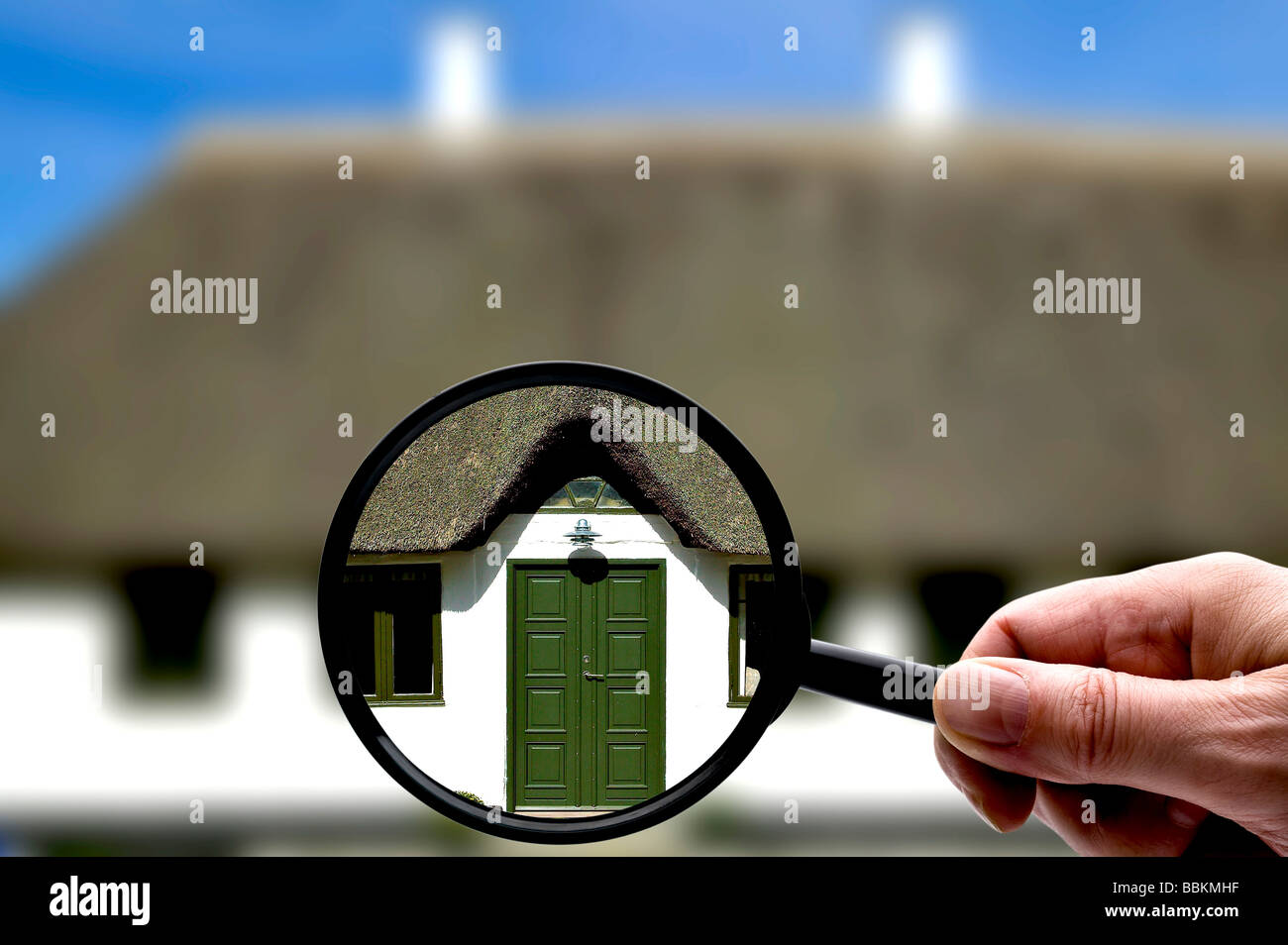 Closer look at an old thatched house with a magnifying glass - Stock Image