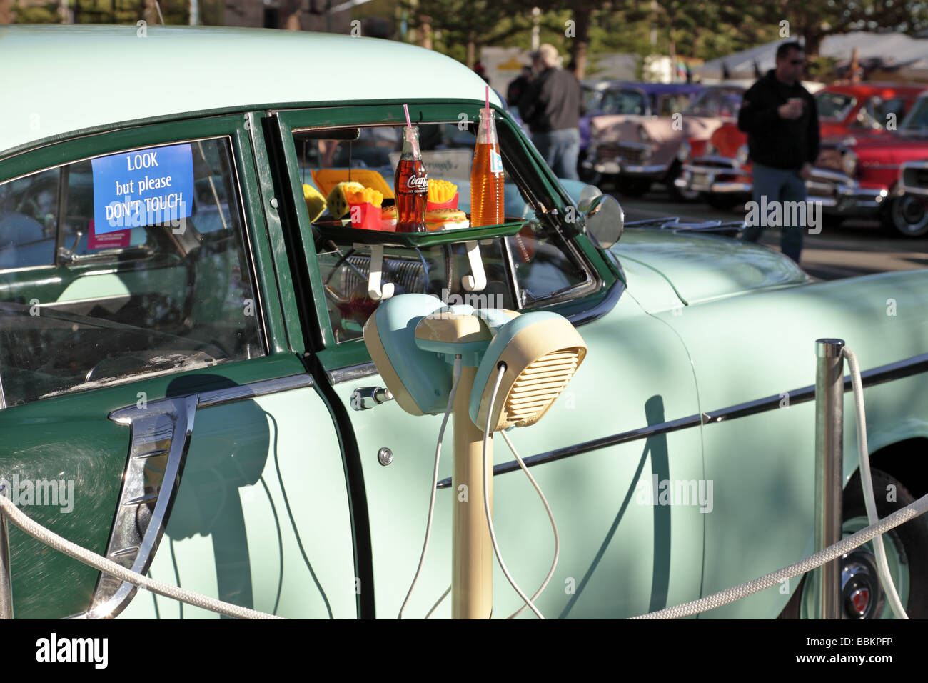Vintage car with fifties drive in speakers and tray of food